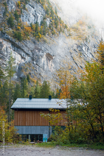 Foto op Canvas Herfst Small wooden house on foot of the mountain. Colorful Autumn forest. Hallstatt, Austria