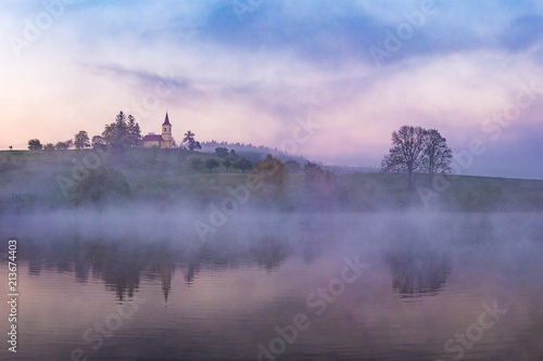 Poster Morning with fog Mystical and dramatic scene. A small on a hill reflected in nearby lake. Beautiful colorful morning light before sunrise. Amazing landscape.