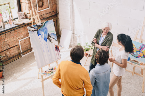 High angle portrait of artists presenting watercolor painting to audience in art studio