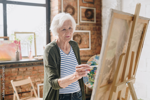 Waist up portrait of white haired senior woman holding palette painting pictures at easel in  art studio standing against windows in sunlight, copy space