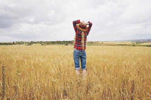 Fotografie, Obraz  Vista posterior de una mujer joven en un campo de trigo