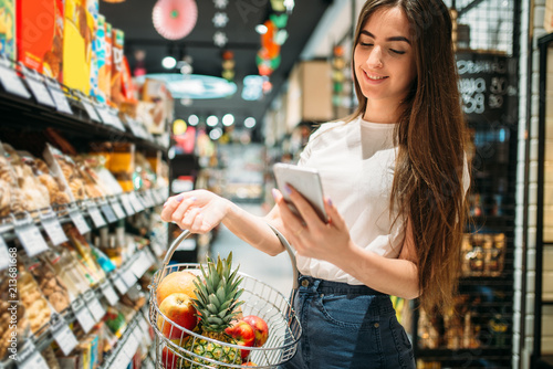 Female customer uses mobile phone in supermarket