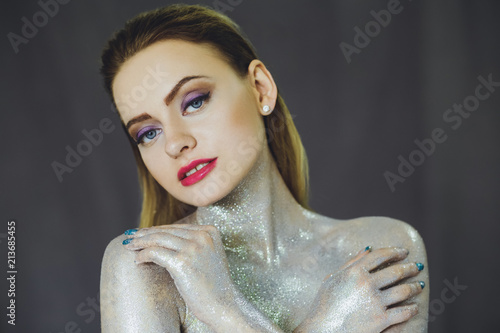 Fototapeta Beautiful girl with creative glitter makeup with sparkles. Beauty is an art face. Photo taken in the studio. obraz