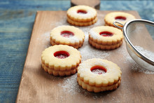 Traditional Christmas Linzer Cookies With Sweet Jam And Sugar Powder On Wooden Board