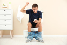 Young Man Using Mobile Phone While Sitting On Toilet Bowl At Home