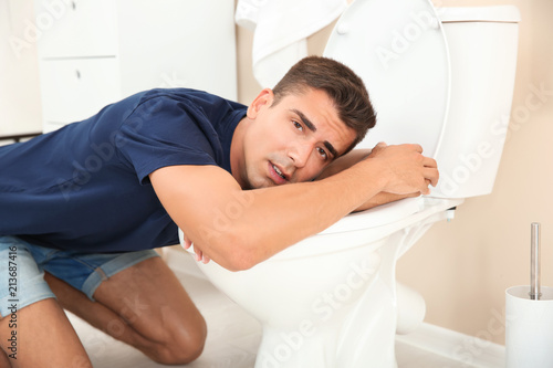 Fotografie, Obraz  Young man vomiting in toilet bowl at home