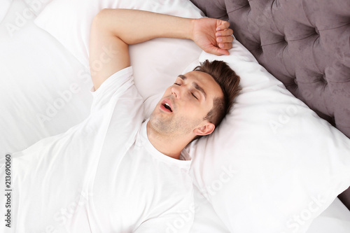 Photo Young man sleeping in bed at home, top view