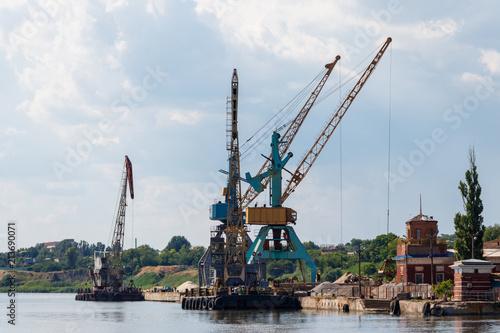 In de dag Poort Heavy cranes in cargo port on the riverbank