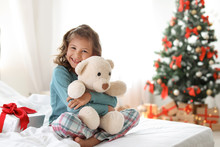 Cute Little Child With Toy Bear And Christmas Gift Box Sitting On Bed At Home