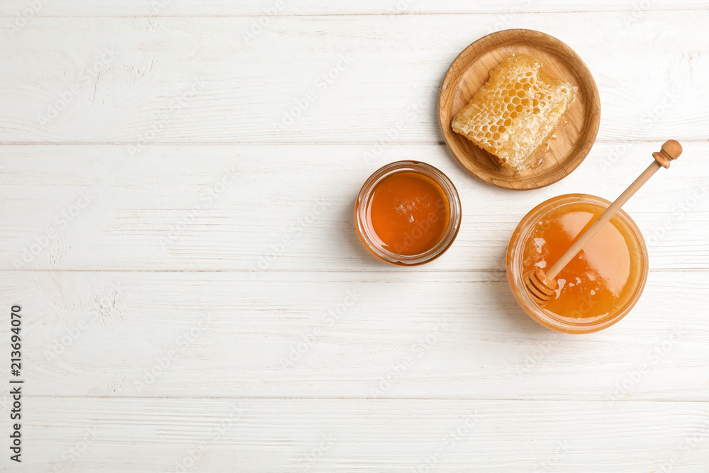 Flat lay composition with fresh honey on wooden background
