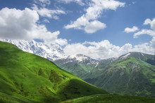 Landscape Of Mountains And Grassy Hills On Sunny Summer Day In Svaneti, Georgia. Blue Sky And White Clouds Over Georgian Mountain. Hills And Mounts Covered Green Grass. Scenic Georgian Wild Nature.