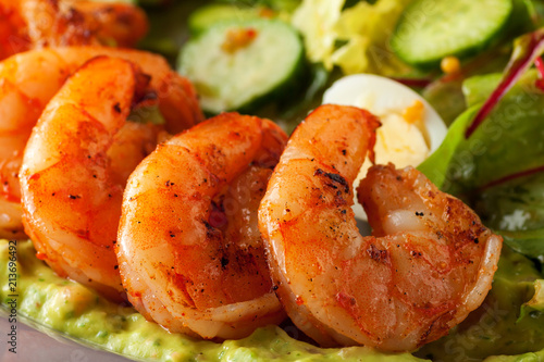 Foto auf Leinwand Schalentier Delicious grilled shrimps served with salad with green vegetables - lettuce, cucumber