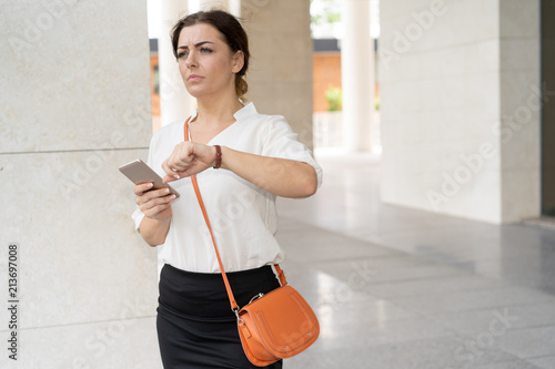 Fotografie, Obraz  Worried woman looking at watch and running to work