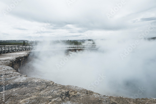 Smoke emitting from hot spring against cloudy sky at Yellowstone National Park