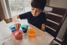 Boy Making Easter Eggs On Table While Sitting At Home