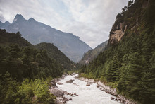 Scenic View Of River Flowing Amidst Mountains Against Cloudy Sky At Sagarmatha National Park