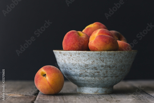 Close up of peaches in bowl on wooden table against black background
