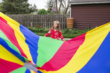Girl Standing By Colorful Para...