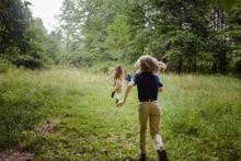 Rear View Of Siblings Running ...