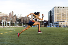 Side View Of Female Athlete Running On Grassy Field Against Sky