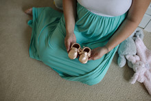 Low Section Of Pregnant Woman Holding Baby Shoe While Sitting At Home
