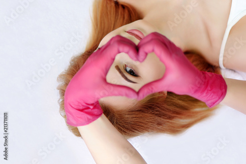 Beautiful laying woman looking through the hands in gloves in a shape of heart Fototapeta