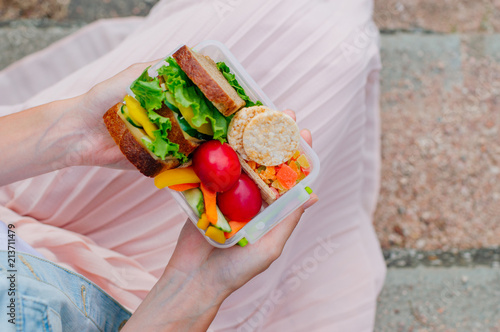 Foto op Aluminium Assortiment Close up of young girl holding lunch box filled with sandwich, crispbreads, fruits and vegetables