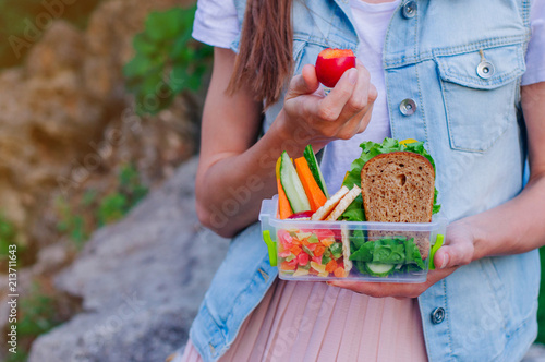 Foto op Aluminium Assortiment Close up of young woman eating plum from lunch box filled with sandwich, fruits and vegetables