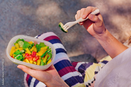 Foto op Aluminium Assortiment Closeup of young woman eating from lunch box filled with salad
