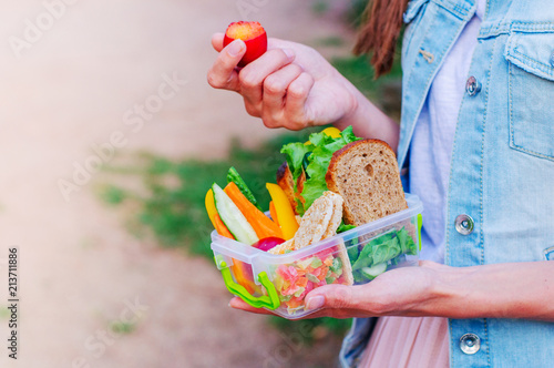 Foto op Aluminium Assortiment Young hipster girl eating from lunch box outdoor