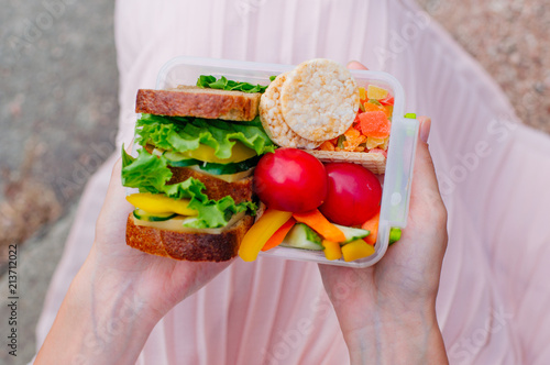 Foto op Aluminium Assortiment Young girl holding lunch box filled with sandwich