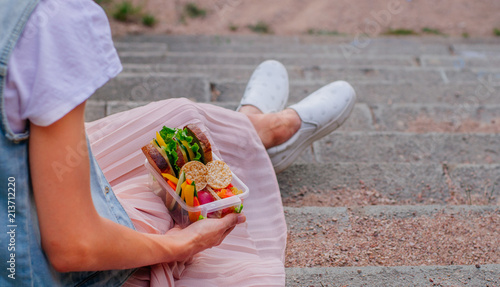Foto op Aluminium Assortiment Young hipster girl holding lunch box sitting on stairs outdoor