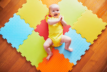 Smiling Baby Girl Lying On Play Mat