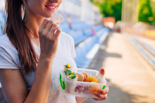 Young Woman Eating From Lunch Box Outdoor