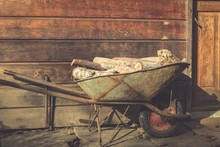 Wheelbarrow With Firewood Pieces By Front Door Of Wooden House. Rural, Countryside House Concepts. Vintage Effect
