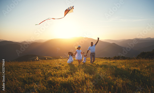 Spoed Foto op Canvas Wanddecoratie met eigen foto Happy family father, mother and children launch kite on nature at sunset