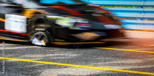 Fotografía  Motor sport car racing on asphalt road with blue fence and yellow line traffic sign