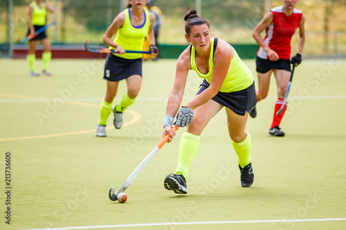 Fotografiet  Young hockey player woman with ball in attack playing field hockey game