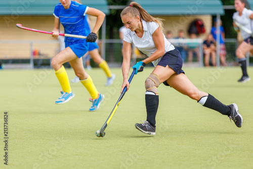 Fotografie, Tablou  Young hockey player woman with ball in attack playing field hockey game