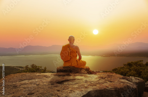 Buddhist monk in meditation at beautiful sunset or sunrise background on high mo Fotobehang