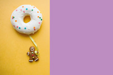 Gingerbread Man Holds A Donut In His Hand That Looks Like A Balloon. Creative Idea. Holiday Concept. Nearby Place For Text