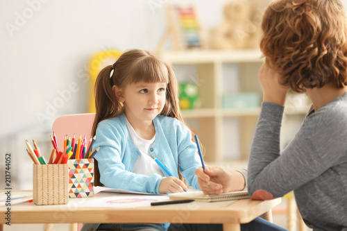 Fotografering Female psychologist with cute little girl during art therapy