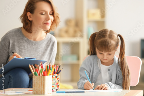 Fototapeta Female psychologist with cute little girl during art therapy
