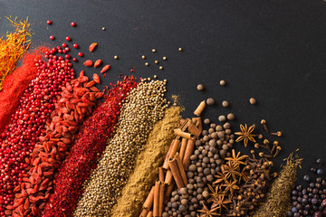 Panel Szklany Do kuchni Colorful spice background for website headers or food labels. Collection of herbs and herbs are scattered on black table.