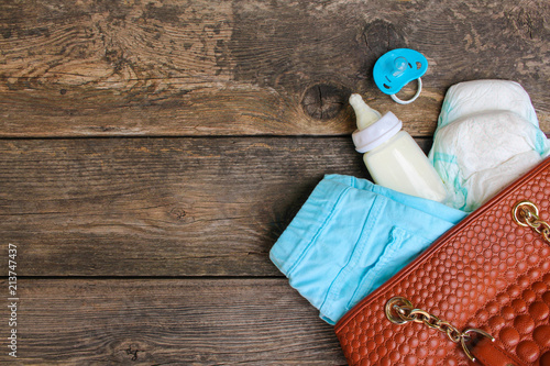 Fotografiet  Women's handbag with items to care for the child on old wooden background