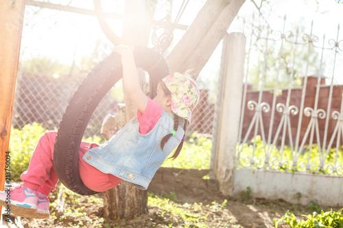 Valokuva  Happy Llittle girl playing swing at park