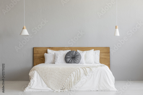 Fotografia, Obraz Knit blanket on wooden bed against grey wall in minimal bedroom interior with lamps