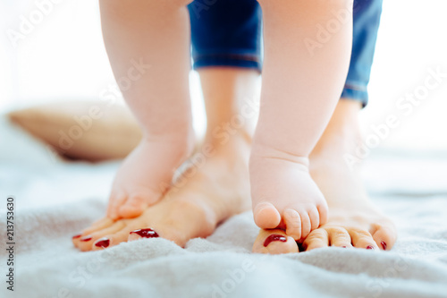 Fotografia  Step by step. Little feet being bare while touching mother