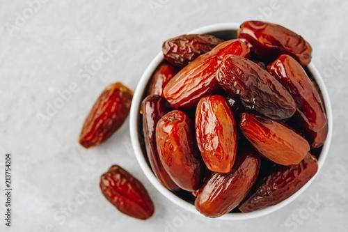 Valokuva  Dried dates in white bowl on grey background
