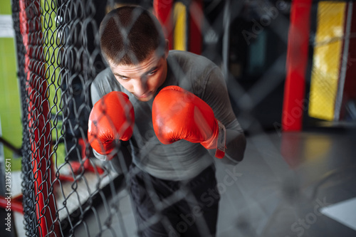 Papiers peints Rouge, noir, blanc Male boxer engaged in training in the gym, in a cage for a fight without rules, Boxing coach